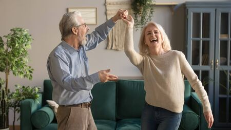 Photo pour Joyful active old retired romantic couple dancing laughing in living room, happy middle aged wife and elder husband having fun at home, smiling senior family grandparents relaxing bonding together - image libre de droit