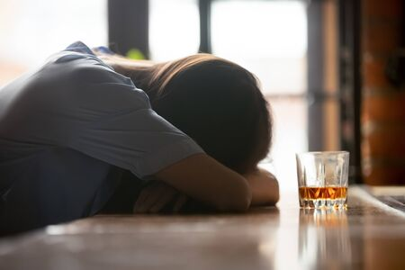 Foto per Drunk intoxicated woman sleeping on bar counter near whiskey glass in the morning, female heavy drinker alcoholic passed out lying asleep after booze, alcoholism problem, alcohol addiction concept - Immagine Royalty Free