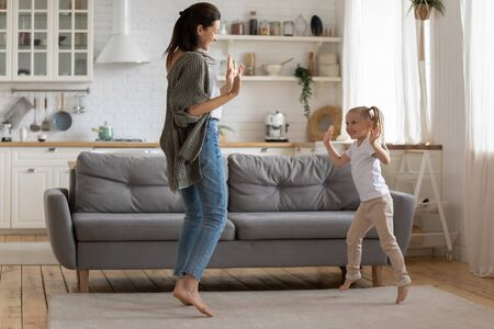 Photo pour Full-length image lively young mommy dancing with preschool cute daughter in cozy light living room at home, family having fun moving barefoot child girl repeats mothers movements enjoy time together - image libre de droit