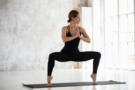 Foto de Beautiful young woman wearing black sportswear practicing yoga, standing in Goddess pose on mat, Sumo Squat exercise, attractive sporty girl working out in modern yoga studio with big windows - Imagen libre de derechos