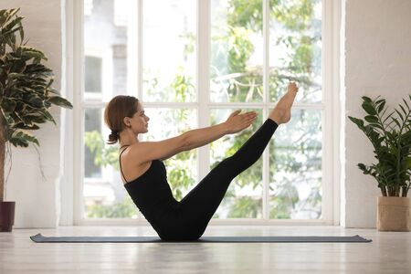 Photo for Beautiful young woman doing Paripurna Navasana exercise, boat pose, practicing yoga, attractive girl wearing black sportswear working out at home or in yoga studio with big window and plants - Royalty Free Image