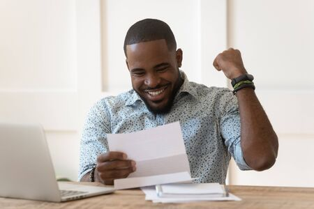 Foto de Happy euphoric young african american guy received paper report, university admission letter, celebrating important goal achievement, banking loan approval, full credit repayment, lottery win notice. - Imagen libre de derechos