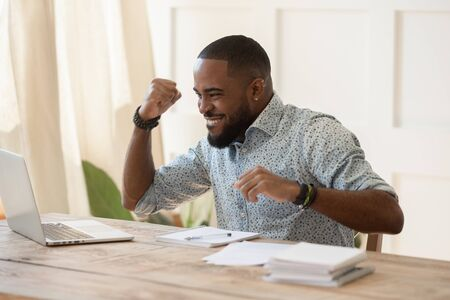 Foto de Euphoric young black man celebrating online lottery win, excellent educational online courses tests results, successful qualification training, getting remote dream work, received high paid job offer. - Imagen libre de derechos