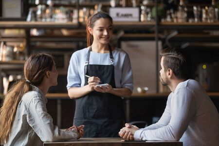 Foto de Young couple making order in cafe, attractive smiling waitress serving customers, writing in notepad, coffeehouse female worker talking with man and woman about menu, offering food and drinks - Imagen libre de derechos