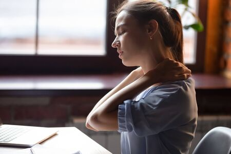 Foto de Tired woman feeling pain in neck pain after sedentary work with computer in uncomfortable posture or chair, exhausted female student or freelancer massaging tensed neck muscles, close up - Imagen libre de derechos
