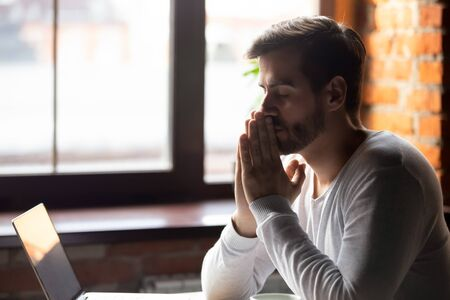 Foto de Worried man thinking about problem solution, pondering important question, puts hands together in prayer, upset sitting alone with closed eyes, frustrated about difficulties, taking break, breathing - Imagen libre de derechos