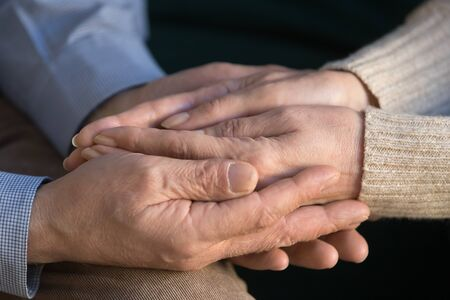 Photo pour Close up elderly husband holding his wife wrinkled hands, supporting, caring, expressing love and mutual understanding, tenderness, senior man comforting old woman, married couple compassion. - image libre de droit