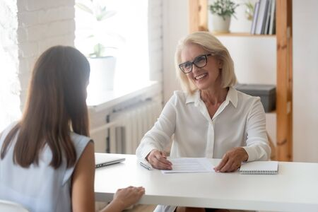 Photo for Happy senior businesswoman or consultant speak with millennial girl applicant having interview in office, smiling aged female boss or CEO talk with young woman candidate making good first impression - Royalty Free Image