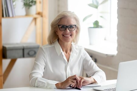 Photo pour Portrait of happy confident senior grey-haired businesswoman in spectacles sit at office desk look at camera smiling, overjoyed glad aged woman worker wear glasses posing making picture at workplace - image libre de droit