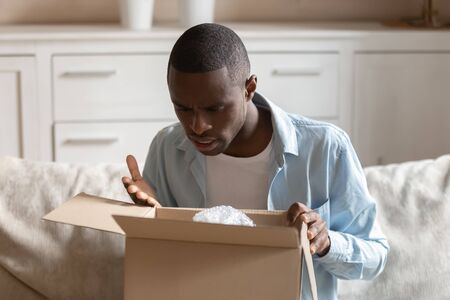 Photo for Frustrated mad african American man unpack cardboard box post shipping parcel with wrong order, disappointed male customer feel confused upset with poor quality and bad delivery service - Royalty Free Image