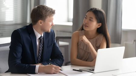 Photo for Young happy concentrated chinese female intern asking confident middle aged male team leader questions about work. Diverse coworkers sitting together at office with computer, discussing project ideas. - Royalty Free Image