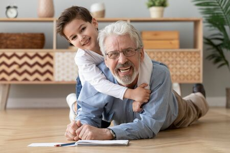 Foto de Happy two 2 generations family old grandfather and cute little boy grandson drawing with pencils lying on warm heated wooden floor together, smiling senior grandpa play with grandchild look at camera - Imagen libre de derechos