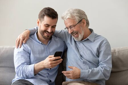 Foto de Happy two age generations men family old father embracing young grown adult son having fun, enjoying using smart phone bonding watching funny social media video using mobile apps at home sit on sofa - Imagen libre de derechos