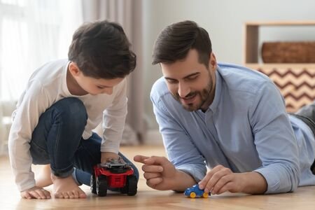 Photo pour Playful happy young single father and cute little son racing holding toy cars on warm heated floor at home, small preschool child boy having fun bonding with dad playing funny game activity together - image libre de droit