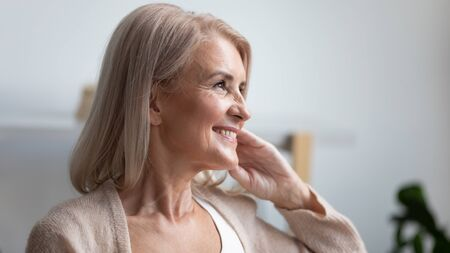 Foto de Close up profile portrait smiling mature woman dreaming, thinking about good future, beautiful retired older female with healthy toothy smile looking in distance, feeling satisfied, natural beauty - Imagen libre de derechos