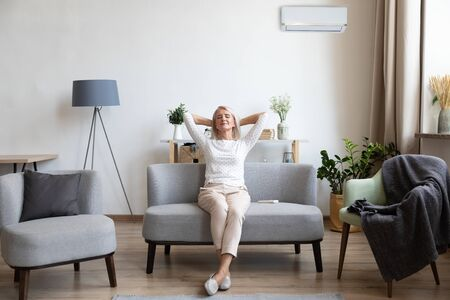 Photo pour Relaxed satisfied older woman sitting leaning back on couch in air conditioner room, happy peaceful mature female with hands behind head resting on sofa at home, enjoying fresh air, breathing - image libre de droit