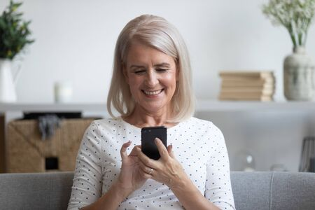 Foto de Smiling mature woman holding phone, using mobile device apps, looking at screen, happy older female chatting online, texting, writing message on cellphone, having fun at home, sitting on couch - Imagen libre de derechos