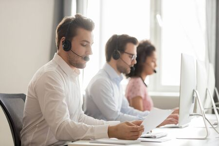 Foto de Diverse call center workers sitting in row in shared room wearing headset use computer, focus on guy hold paper read document, sales process and customer service assistance support guidelines concept - Imagen libre de derechos