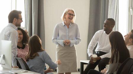 Photo pour Laughing old coach team leader talking with diverse coworkers chatting at business meeting, friendly multi racial office workers and middle aged woman ceo have fun conversation at coffee break concept - image libre de droit