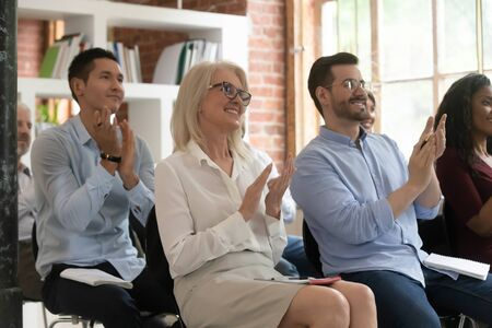 Photo for Grateful diverse employee sit at company seminar or training clap hands thanking presenter for lecture, smiling happy multiracial colleague or businesspeople applaud for successful presentation - Royalty Free Image