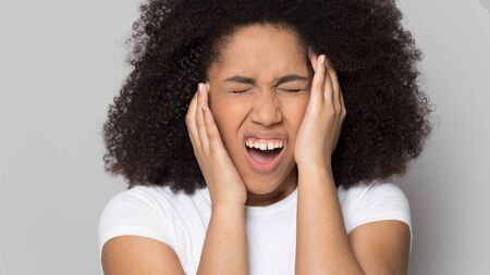 Foto de Unhealthy african American young woman isolated on grey studio background suffer from migraine, unwell depressed biracial millennial girl touch head struggle with headache, health problem concept - Imagen libre de derechos