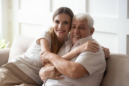 Photo pour Adult granddaughter and elderly 80s grandfather sitting together on couch posing look at camera, loving intergenerational family portrait warm love and care between people different generation concept - image libre de droit