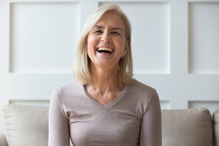 Photo for Vivacious elderly 60s blond woman with wide toothy candid smile sit on sofa look at camera head shot portrait, having video call lively positive conversation with friend via online application concept - Royalty Free Image