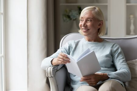 Photo pour Distracted from reading novel or story happy mature lady looking away, out of window. Smiling older woman imagining book heroes stories, dreaming, enjoying weekend, sitting on sofa alone at home. - image libre de droit