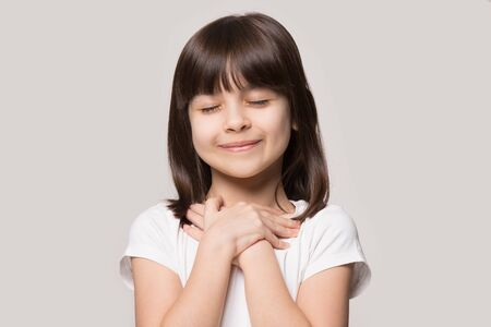 Photo pour Close up of cute happy small girl isolated on grey studio background hold hands at heart chest feel grateful, smiling little child with eyes closed pray thanking god high powers, faith concept - image libre de droit