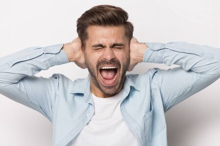 Foto de Close up of furious caucasian young man isolated on grey studio background close ears scream bothered by loud noise, angry mad male shout yell lose patience ignoring avoiding noisy unbearable sound - Imagen libre de derechos