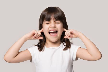 Foto de Annoyed little brunette girl isolated on grey studio background close plug ears scream loudly tired by noisy sound, furious angry small child shout yell avoid ignore unbearable loud noise ask quiet - Imagen libre de derechos