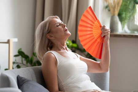 Foto de Stressed annoyed old senior woman using waving fan suffer from overheating, summer heat health hormone problem, no air conditioner at home sit on sofa feel exhaustion dehydration heatstroke concept - Imagen libre de derechos