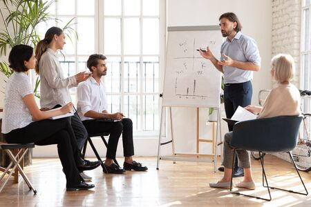 Photo for Focused male company ceo coach mentor speak to multiethnic staff people presenting new corporate strategy, confident businessman trainer speaker give flip chart presentation at company training - Royalty Free Image