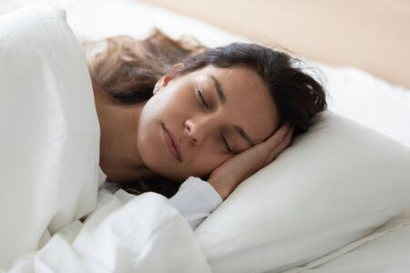 Photo pour Head shot close up side view tranquil young biracial woman lying in bed, covered with fresh linen, enjoying lazy weekend time. Pretty girl relaxing with closed eyes, feeling peaceful at home. - image libre de droit