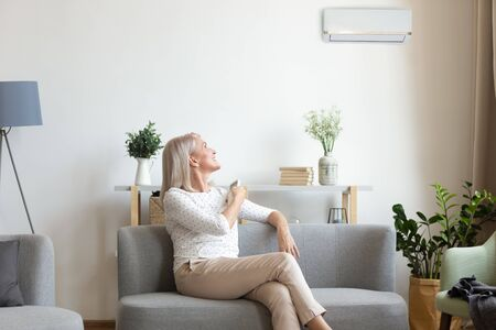 Foto de Middle aged old happy woman holding remote climate control switch on air conditioner on wall sit on sofa in living room enjoy cool fresh air condition system at convenient modern home relax on couch - Imagen libre de derechos
