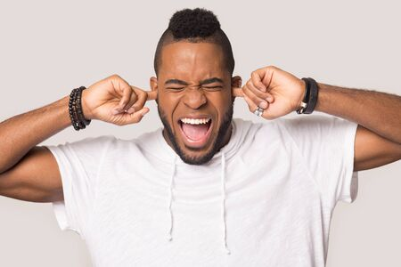 Foto de Furious african American millennial man isolated on grey studio background plug ears avoid loud disturbing noise, mad angry biracial male scream yell feel stressed annoyed by noisy sound - Imagen libre de derechos