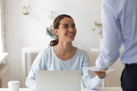 Foto de Head shot young happy mixed race female employee taking envelope with money reward from male boss team leader. Smiling biracial manager satisfied with cash bonus for great work performance at office. - Imagen libre de derechos