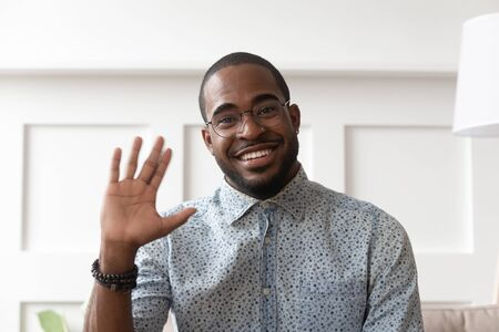 Foto de Smiling african American millennial man in glasses look at camera waving saying hello talking on video call, happy black male vlogger in spectacles greeting with subscribers shooting video blog - Imagen libre de derechos