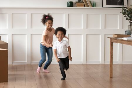 Foto de Excited smiling preschooler kids run in new empty home feel happy to move, overjoyed small brother and sister laugh have fun chasing each other playing in living room together. Entertainment concept - Imagen libre de derechos