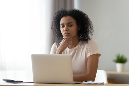 Foto de Pensive african American young woman sit at desk thinking studying or working on laptop at home, thoughtful black millennial girl student pondering considering idea looking at computer screen - Imagen libre de derechos