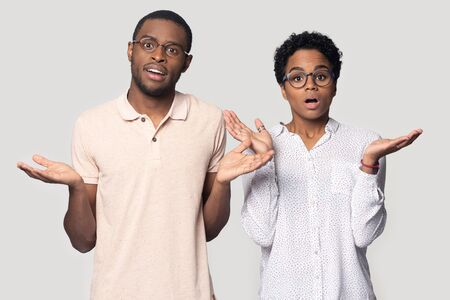 Photo pour Head shot portrait close up shocked African American man and woman in glasses shrugging shoulders, lifting hands, feeling confused, puzzled young couple looking at camera, isolated on grey background - image libre de droit