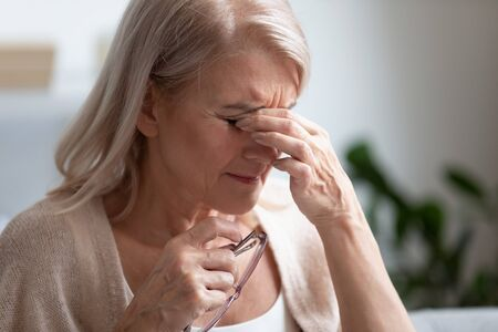 Photo pour Tired upset middle aged older woman taking off glasses rubbing dry eyes massaging eyelids feeling eyestrain fatigue concept, exhausted mature senior lady suffer from bad vision sight pain problem - image libre de droit