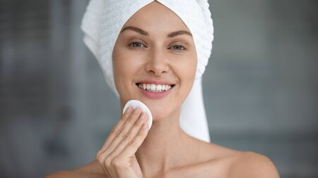 Foto de Smiling beautiful young woman with towel on head hold cotton pad disk cleansing face skin with cleanser, happy lady remove makeup look at camera enjoy healthy clean skincare beauty treatment concept - Imagen libre de derechos