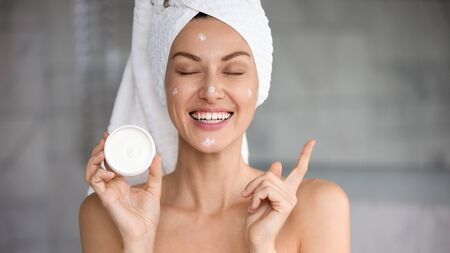 Photo pour Funny smiling attractive young woman with towel on head creme on face eyes closed hold cream jar point finger at copy space advertise healthy dry skin care moisturizing beauty spa treatment concept - image libre de droit