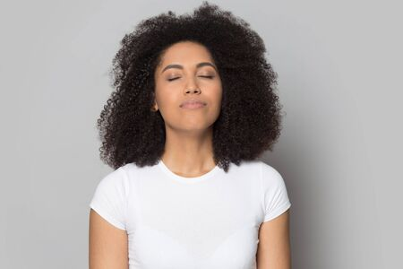 Photo pour Head shot close up relaxed African American girl with closed eyes breathing deep, meditating, dreaming about future, isolated on grey studio background, mindful female enjoying break, pause - image libre de droit