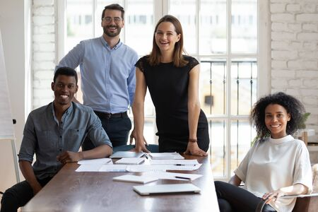 Photo for Portrait of confident young happy multiracial business people posing for photo. Successful team of mixed race employees looking at camera. Joyful millennial diverse professionals gathered near table. - Royalty Free Image