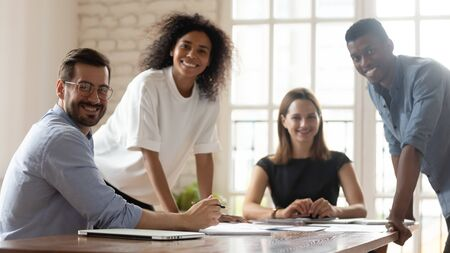 Photo for Head shot portrait young happy mixed race group of professionals sitting at table in modern office. Smiling multiracial leaders executives employees corporate people workers looking at camera. - Royalty Free Image