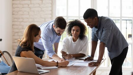 Photo for Smiling mixed race colleagues leaning over table, explaining project ideas to female teammates. Happy managers working with project statistics or marketing strategy at brainstorming meeting at office. - Royalty Free Image