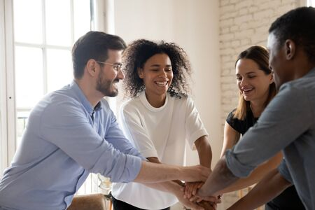 Photo for Overjoyed multiracial group of young employees engaged in funny teambuilding activity. Happy mixed race teammates putting hands together, demonstrating support unity, celebrating success at office. - Royalty Free Image