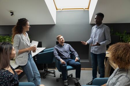 Photo for Interested multiracial group of employees listening to confident young african american male team leader, presenting project ideas or sharing information at coworking office. Brainstorming concept. - Royalty Free Image